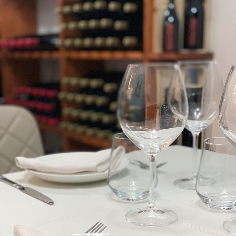 un bicchiere in primo piano su un tavolo, sullo sfondo scaffali con bottiglie di vari vini